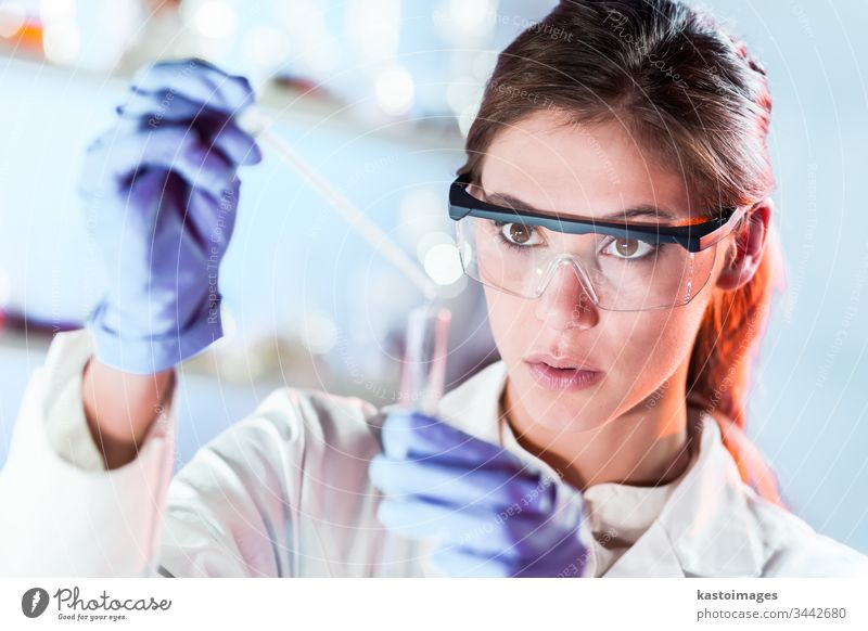 Female researcher pipetting solution into test tube in life science laboratory. woman scientist technology analysis experiment analyzing biotechnology