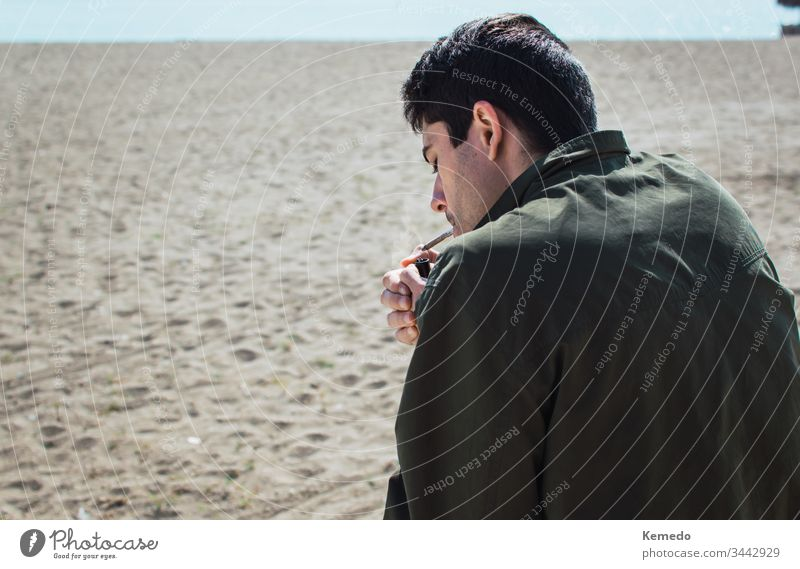 Young man smoking a marijuana joint or cigarette on the beach during a sunny day. Blur background and copy space left. person people cannabis smoke weed young