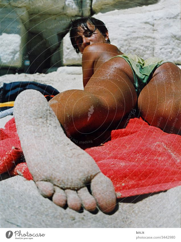 Young woman lies tanned on the beach on a towel, barefoot with sandy feet in the foreground and looks into the camera. Beach Woman Brown Sunbathing Summer