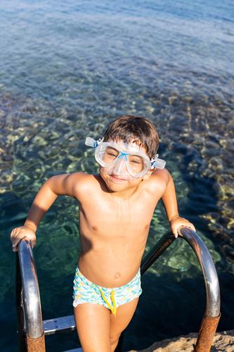 Little boy on a pool ladder going down to bathe in the sea amandakis beautiful blue child childhood clear climbing coast crystal cute diving fun goggles greece