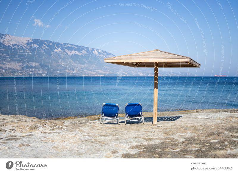 Hammock and umbrella on a rocky beach in Kefalonia, Greece amandakis beautiful blue calm chair coast coastal coastline concept greece hammock holiday idyllic