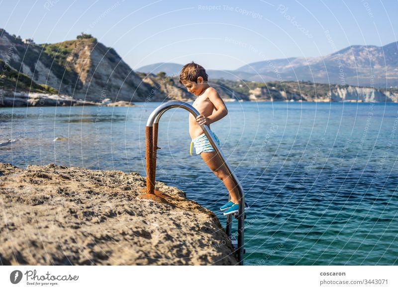 Little boy on a pool ladder going down to bathe in the sea amandakis beautiful blue child childhood clear climbing coast crystal cute diving fun greece