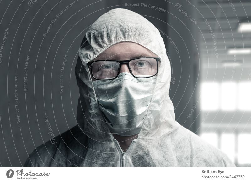 Portrait of a medical doctor in a protective suit and with reflective glasses, depicting an empty hospital care concept coronavirus Corridor Empty peril Dark