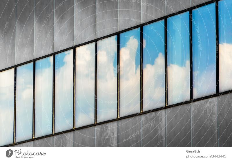 reflection of blue sky and white clouds in the windows of a gray concrete building abstract architecture background blocks business city diagonal empty fragment