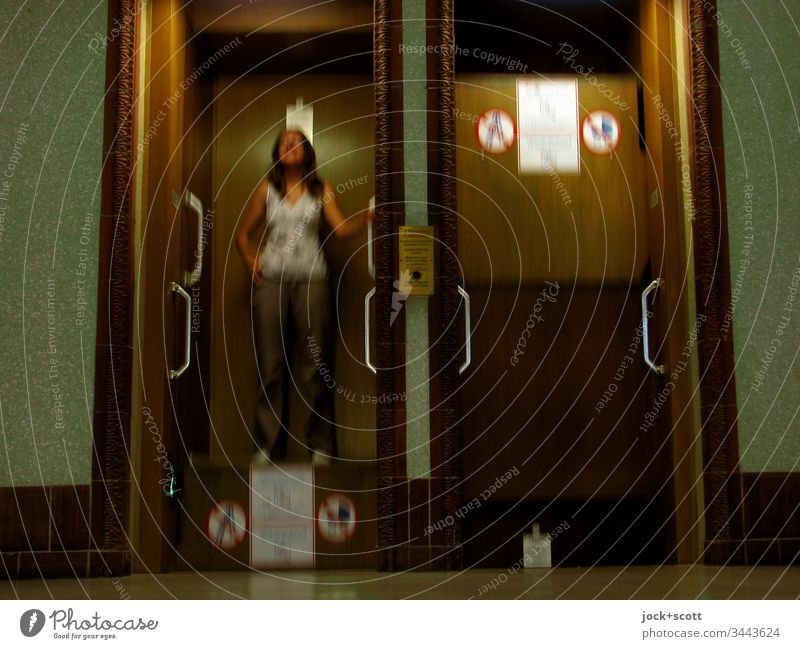 Paternoster gladly takes the young woman with a smile Interior shot Central perspective Colour photo Paternoster elevator Elevator Movement Stand Upward