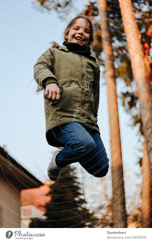 Little girl in flight, she jumps on a trampoline in the garden in front of two pines Small Child Schoolchild Trampoline Hop Jump Flying Garden Joy Playing