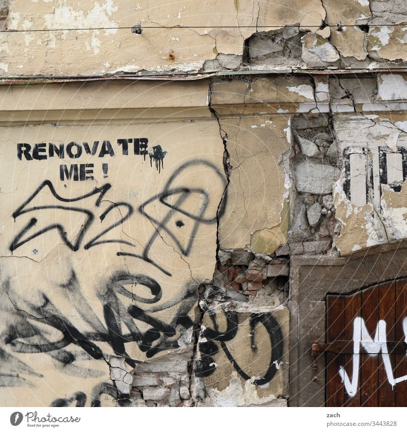 "dilapidated facade of a house with the inscription ""Renovate me"". Past Redecorate Wall (barrier) Wall (building) Colour photo Transience Destruction Broken Old"