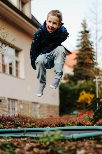 Little boy laughs and jumps on a trampoline in the garden of a house Boy (child) Small Child Schoolchild Trampoline Hop Jump Flying Garden