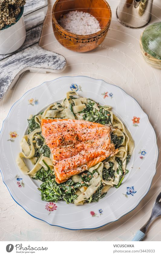 Plate with noodles, salmon and spinach on white rustic table background. Healthy food meal. Dieting. Lunch. Top view plate healthy dieting lunch top view tasty