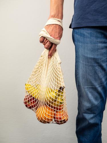Mann hält wiederverwendbare Tasche mit frischen Obst in seiner Hand, gesunde Ernärhung, plastikfrei einkaufen fruit Banane orange apfel Fresh Vitamin