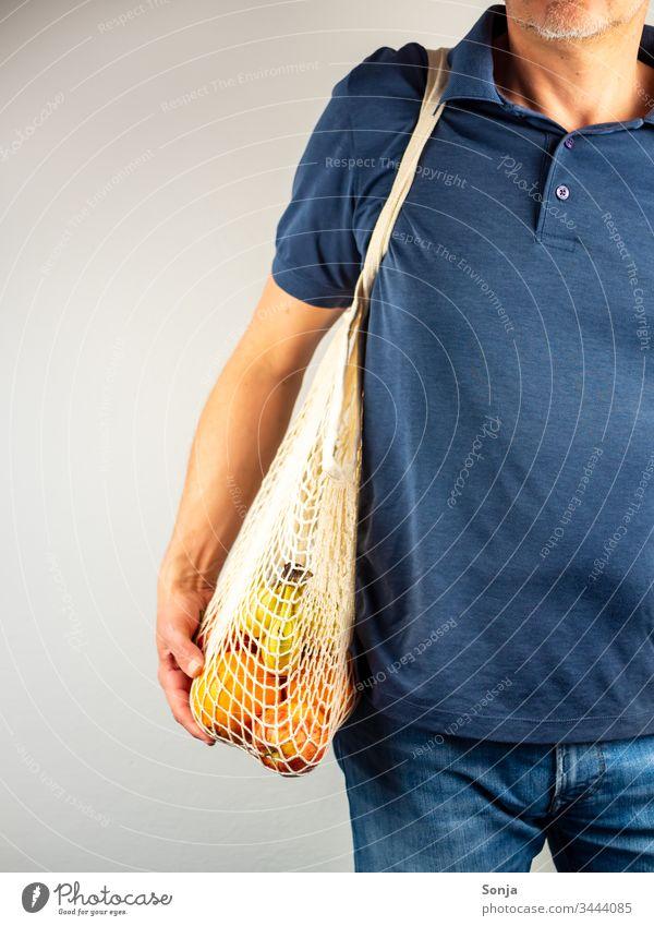 Mann über 40 mit Einkaufsnetz voller Obst über seiner Schulter hängend Banane Orange einkaufsnetz schulter Mannequin hand umwelt
