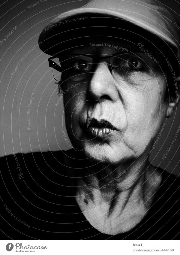 With big eyes the old woman stared into the future, but neither the baseball cap nor the glasses helped, she just couldn't see anything. Woman