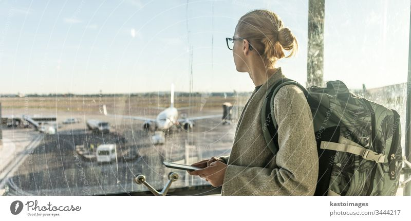 Young woman standing near airport gates window holding cellphone in her hands, wearing travel backpack and walking to lounge area. Female traveler search online map at the airport