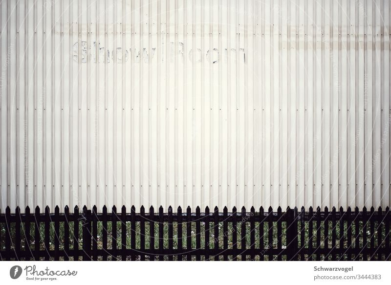 Weathered lettering ShowRoom on metal facade Facade Fence showroom Yellowed vertical structures Industry Commerce