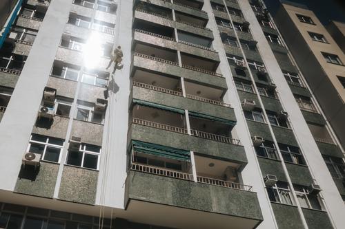 worker cleaning windows of a high-rise apartment block in Rio de Janeiro, Brazil building business city cleaner climb climbing dangerous exterior facade glass