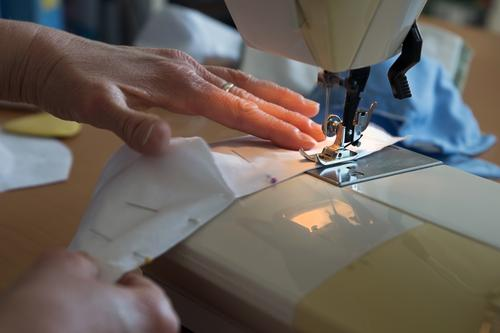 Hands on the sewing machine hold the stitched fabric together and sew lining fabric for a mouthguard / corona thoughts hands Sewing machine Handcrafts Tailoring