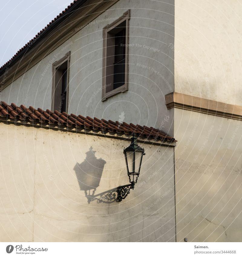 Laterne Lampe Schatten Haus Fassade Mauer Wand Licht Straßenlaterne Stadt Prague urban Fenster Linien und Formen