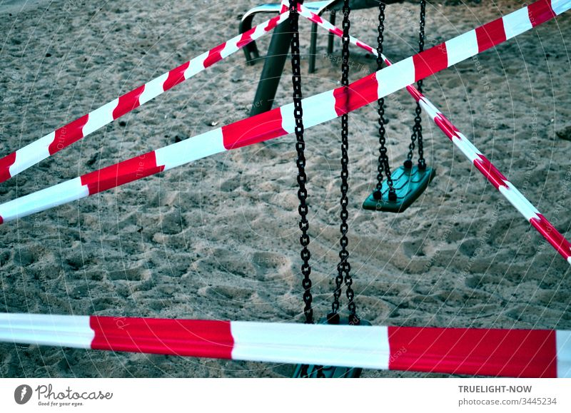 Corona-Thoughts | Red and white signal crime scene flutter tape stretched criss-cross over a children's swing and the sand of a children's playground
