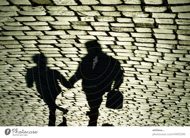 Shadow of two people on the cobblestone Shopping trip city stroll persons Human being Paving stone two persons Hold hands Together Father and Child