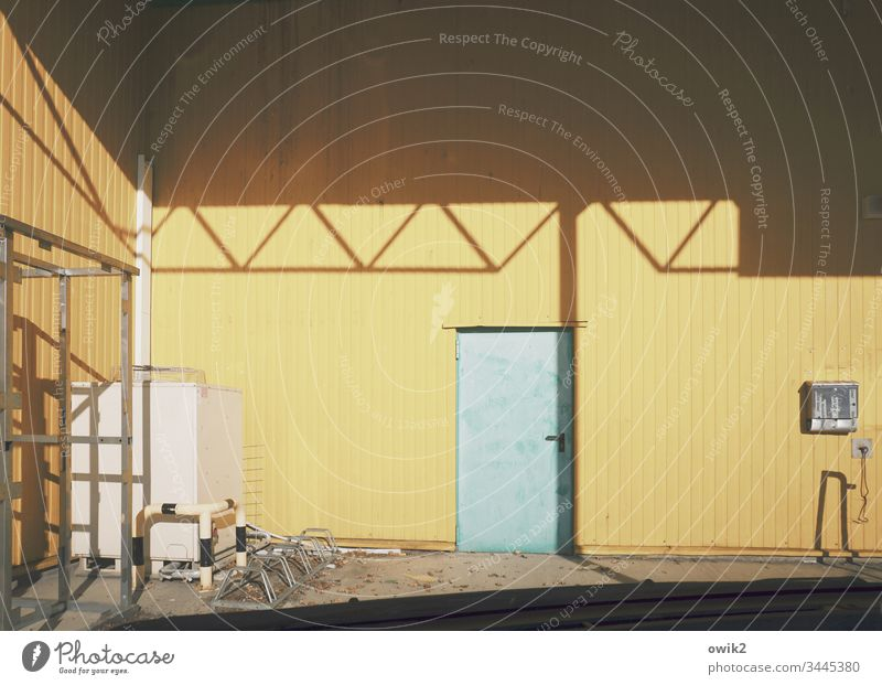 back door Home improvement store Wall (building) Metal Tin sheet metal Yellow Roof Shadow Sunlight Contrast Door worn-out Exterior shot Colour photo Deserted