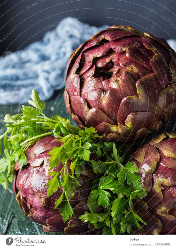Raw artichokes with parsley on dark background raw uncooked drop water vegetable food vegetarian herb ingredient closeup green texture color italian