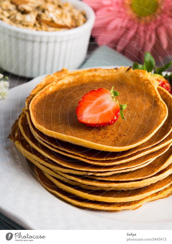 Stack of oatmeal pancakes with strawberries healthy strawberry stack summer spring cook flower breakfast morning flour syrup maple dish plate white table