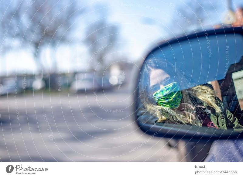 Young woman with mouth guard sitting in the car Woman Mask Rear view mirror Mirror Meditative Driving Respirator mask Car Face mask Town Virus coronavirus