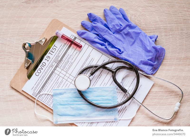 top view of a doctor workspace with protective gloves, protective mask, stethoscope, blood tube and coronavirus test. Covid-19 concept corona virus covid-19