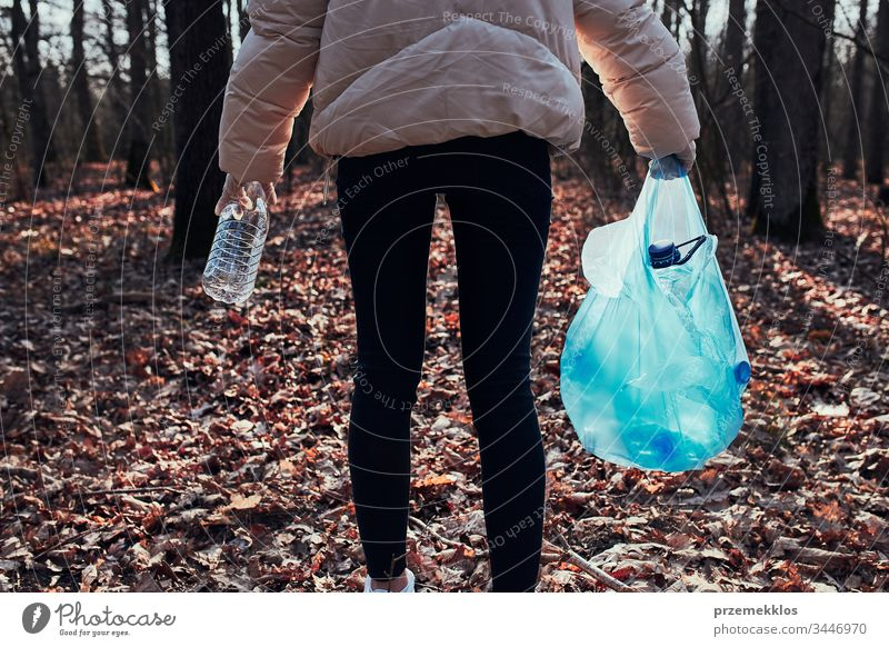 Young woman cleaning up a forest. Volunteer picking plastic waste to bags. Concept of plastic pollution and too many plastic waste. Environmental issue. Environmental damage. Responsibility for environment. Real people, authentic situations