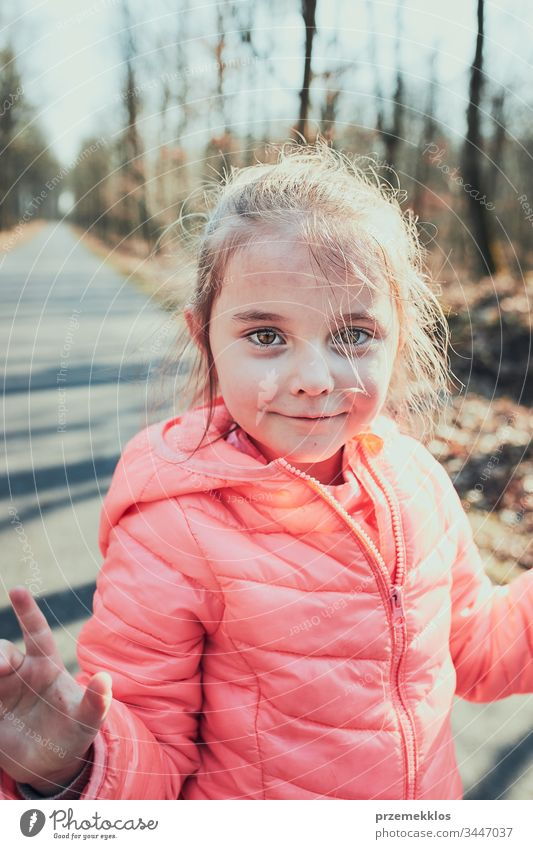 Portrait of little girl playing in the park, having fun on sunny autumn day. Real people, authentic situations kid child happy outdoors childhood forest person