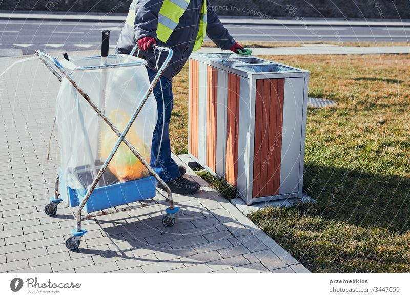 Cleaning service worker emptying the trash. Man wearing yellow vest, cleaning a bin, standing beside a cleaning cart. Real people, authentic situations plastic
