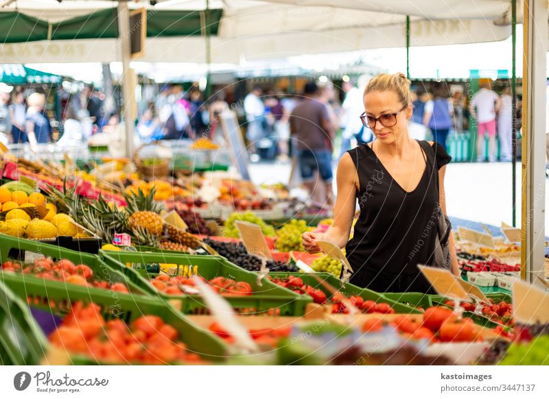 Woman buying fruits and vegetables at local food market. Market stall with variety of organic vegetable woman shopping vegetarian grocery fresh nutrition choice