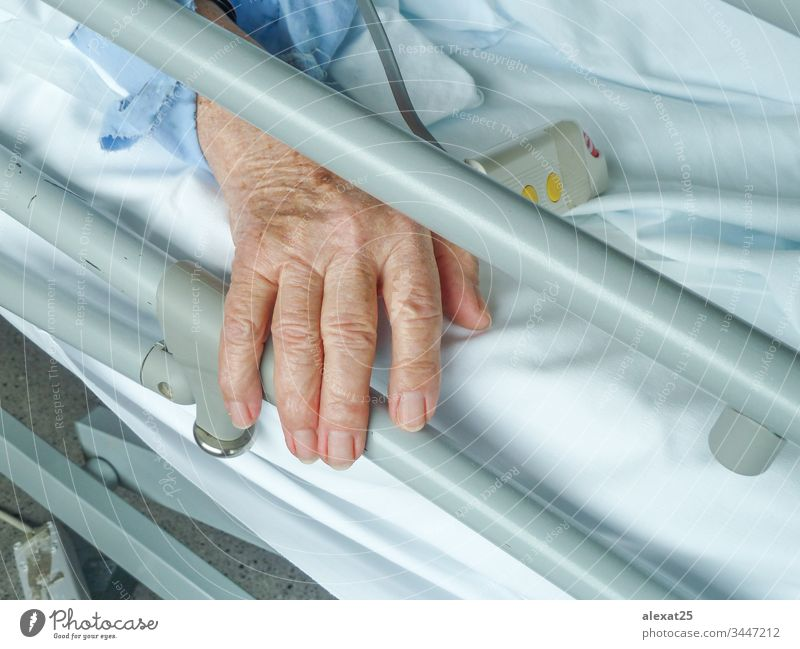 Elderly woman's hand in the hospital adult aged bed care clinic concept cure elderly equipment female grandmother health health care healthy help holding