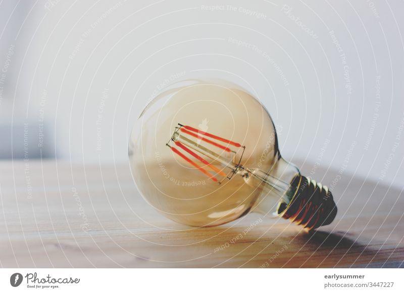 Light bulb in retro look on wooden table Electric bulb Idea Wood lightbulb Retro Retro Colours vintage light source Physics watt luminescence stream Glass
