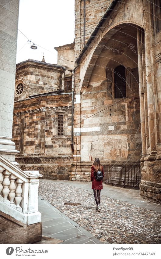 Young woman walking by Bologna Centre architecture backpack belltower bologna bologne bright building city clock coat day distance europe facade from italian