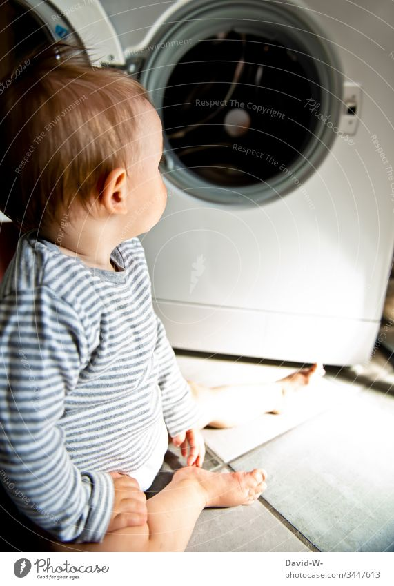 Baby toddler sits interested and curious in front of washing machine on the floor Toddler Washer Cute Child peril Observe inquisitorial Boy (child)