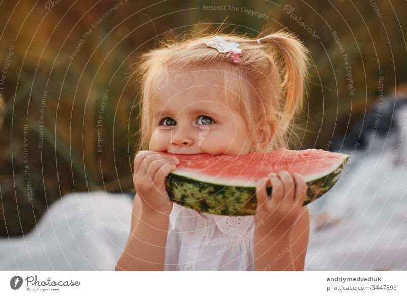 Funny portrait of an incredibly beautiful Red-haired little girl eating watermelon, healthy fruit snack, adorable toddler child with curly hair playing in a sunny garden on a hot summer day. portrait