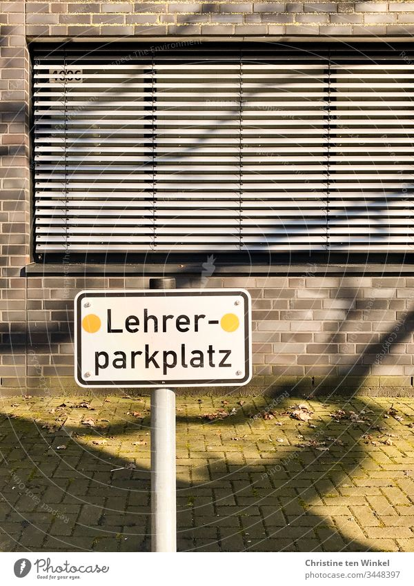 Empty parking lot. A sign 'Lehrerparkplatz' in front of a school building with closed shutters Signage Signs and labeling Characters Parking lot Reserved School