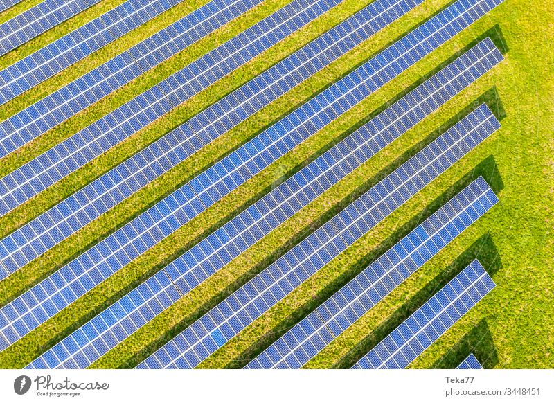 a modern solar cell park from above solar cells sun sun rays sun beams blue white hot yellow grass meadow green clouds reflections lithium modern solar cells
