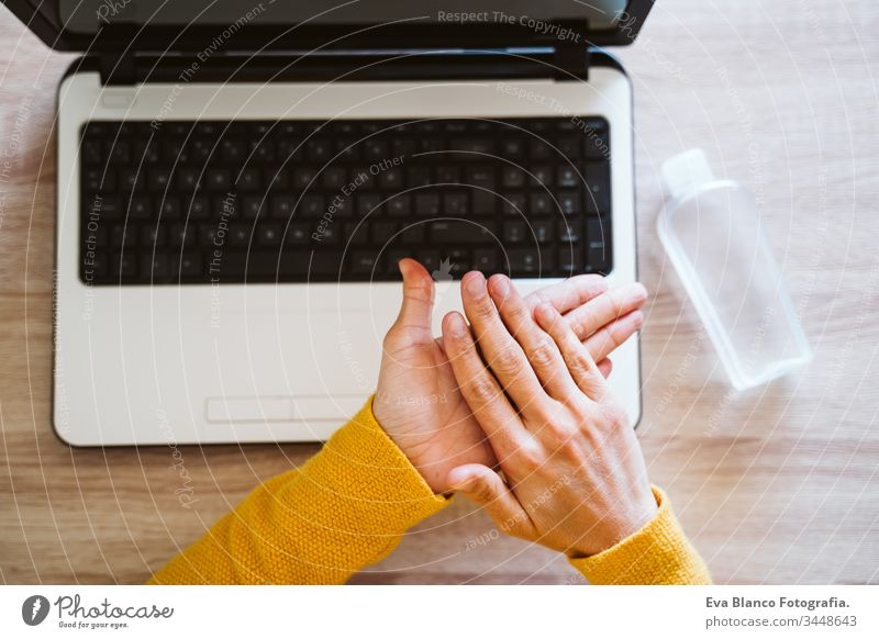 young woman working on laptop at home, using hand sanitizer alcohol gel. Stay home during coronavirus covid-2019 concept disinfectant hands antibacterial