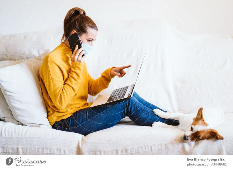 young woman working on laptop at home, sitting on the couch, wearing protective mask. Cute small dog besides. Stay home concept during coronavirus covid-2019