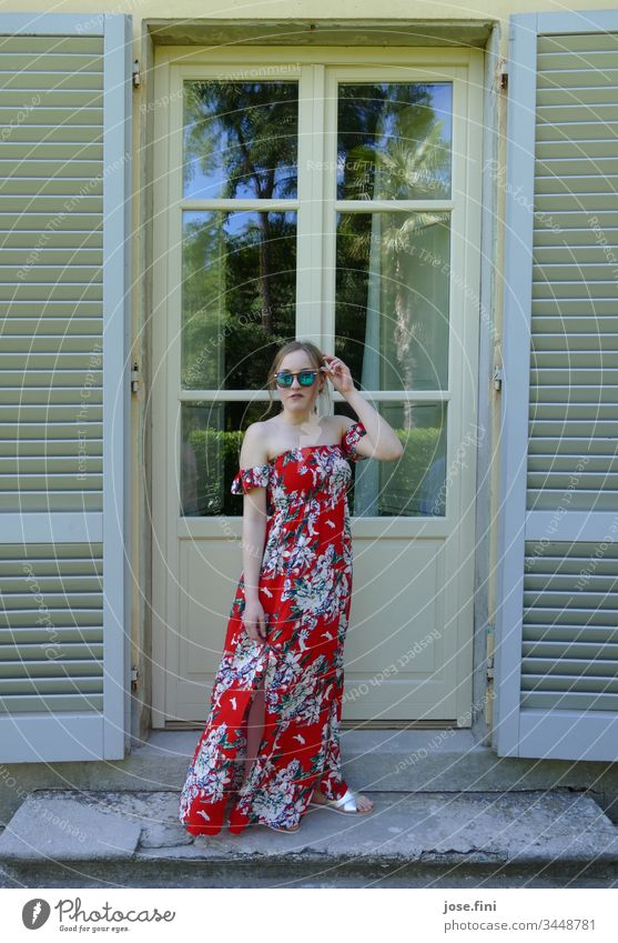 young woman in long summer dress and sunglasses standing in front of an old building door with open wooden shutters Young woman Summer Blonde Slim Feminine