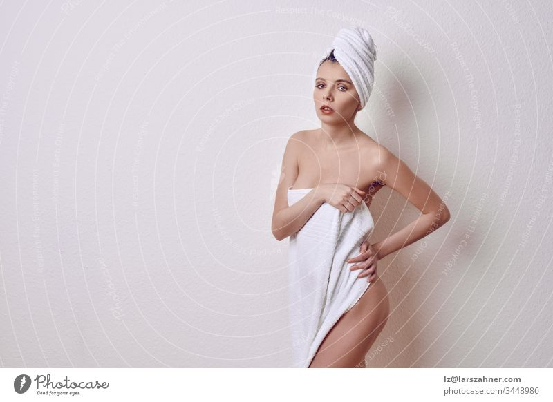Alluring young naked woman covering her breasts and front of her torso with a fresh clean white a towel as she looks at camera with a sultry expression and parted lips over a white studio background