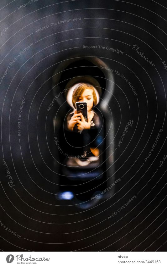 young through the keyhole Boy (child) Keyhole mobile Playing Observe Spy Copy Space left Detail Colour photo Interior shot Looking Human being Eyes Surveillance
