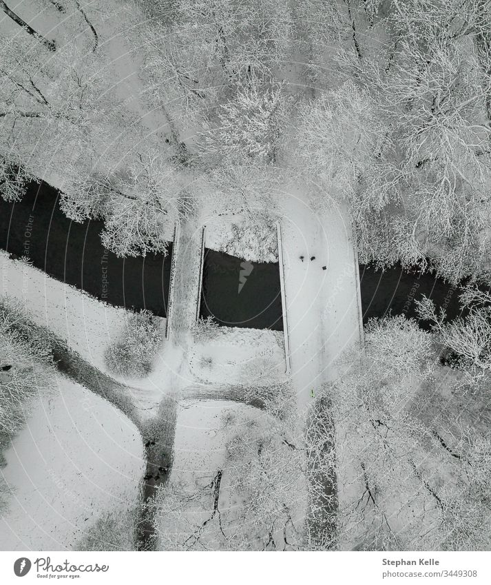 A snowy bridge with walking people high from above in a cold winter scenery. Snow vertical drone aerial tree river angle outdoors landscape park freedom run