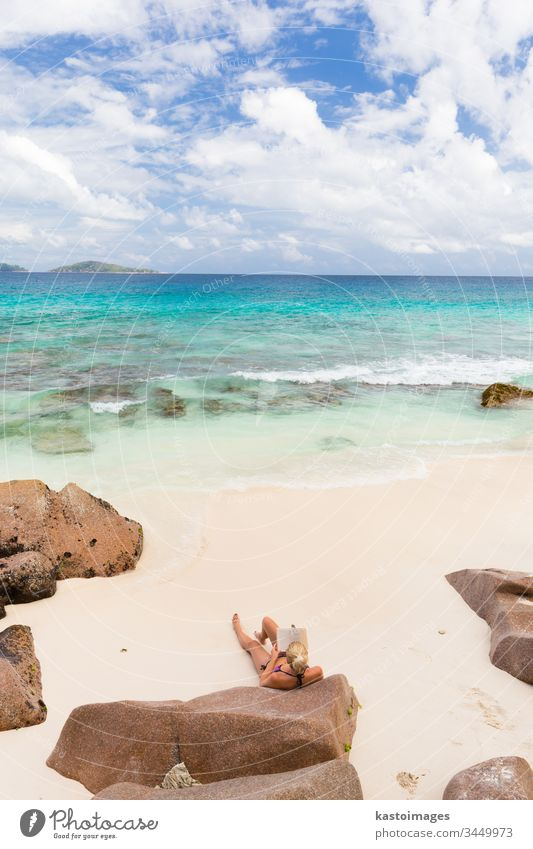 Woman reading book on picture perfect beach Anse Patates on La Digue Island, Seychelles. travel summer vacation woman seychelles lifestyle holiday sea sand