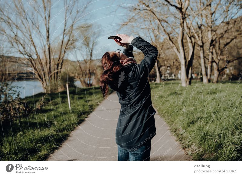 Young woman in nature takes pictures with her smartphone, holding her back in a position that brings sweat stains under the armpits of every orthopaedic surgeon