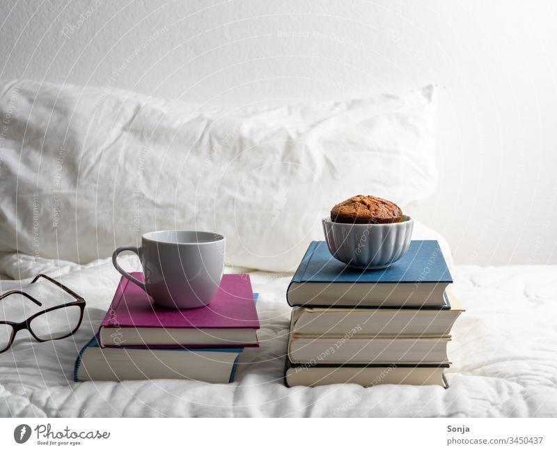 Bücherstapel mit einer Tasse Kaffee und einem Muffin auf einer weißen Bettdecke im Schlafzimmer bücherstapel muffin hygge bettwäsche schlafzimmer Isolated