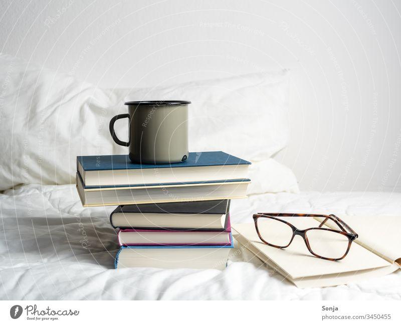 Bücherstapel mit einer Tasse Kaffee und einer Lesebrille auf einer weißen Bettdecke im Schlafzimmer bücherstapel kaffee getränk lesebrille bett bettdecke