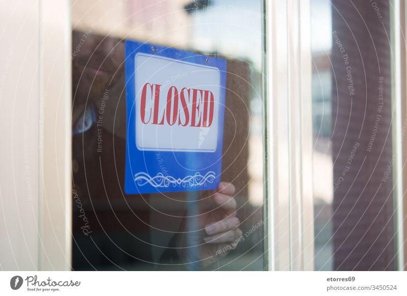 Business man hanging closed sign for coronavirus COVID-19 beard business man caution crisis door employee entrepreneur epidemic glass message notice owner